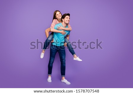 Full length photo of two carefree people guy carrying lady piggyback cheerful free time summer weekend wear casual stylish blue striped t-shirts jeans isolated purple color background #1578707548
