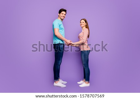 Will you marry me? Full body profile photo of cute couple stand opposite hold hands love confession wear casual blue striped t-shirts jeans isolated purple color background #1578707569