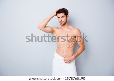 Portrait of masculine brutal masculine guy visit barbershop spa salon enjoy anti dander effect touch his shiny effect stand bath with white towel isolated grey color background #1578765190