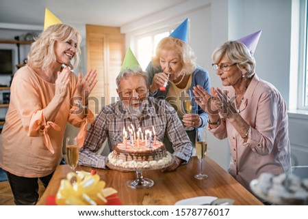 Group of happy mature friends having fun on birthday party while man is blowing candles on a birthday cake.  #1578776017