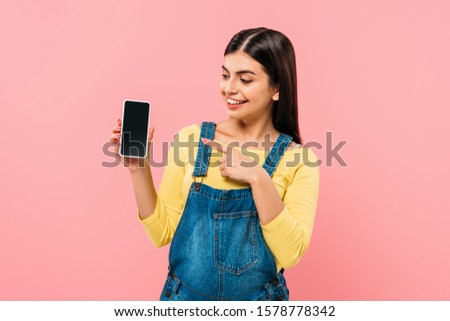 smiling pregnant pretty girl pointing with finger at smartphone with blank screen isolated on pink #1578778342