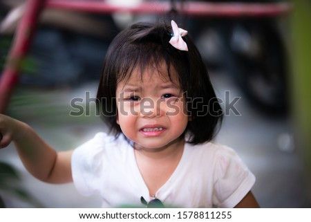 The baby's face was crying with great grief. She cries seriously and frowns. Solid color background. Asian girl 2 years old and 9 months old #1578811255
