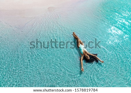 Beautiful slim woman lying on the beach in white swimsuit. Aqua Menthe trendy color of the new year 2020. Leisure island vacations concept. #1578819784