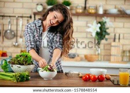 Beautiful girl talking on the mobile phone and smiling while cooking in kitchen at home #1578848554
