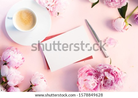 Beautiful fresh pink and white peony flowers on pink table with cup of coffee, frame with copy space on white card for your text, top view and flat lay background #1578849628