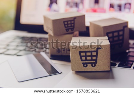 Online shopping - Paper cartons or parcel with a shopping cart logo and credit card on a laptop keyboard. Shopping service on The online web and offers home delivery. #1578853621