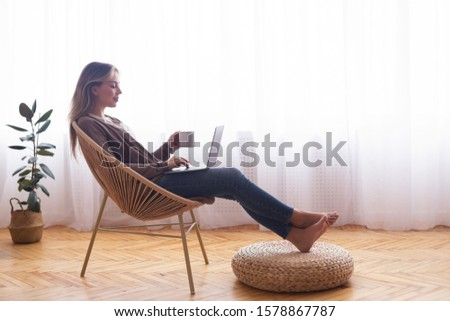 Weekend leisure. Young girl networking on laptop, relaxing with coffee near window, free space #1578867787