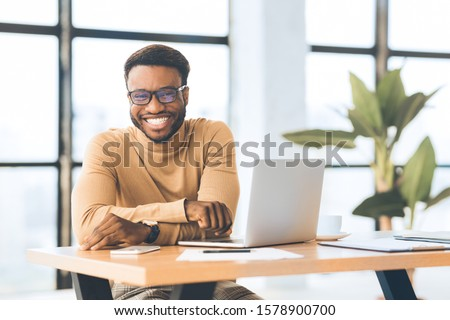 Blogger At Work. Smiling black man looking at camera, sitting at desk with laptop. Selective focus #1578900700