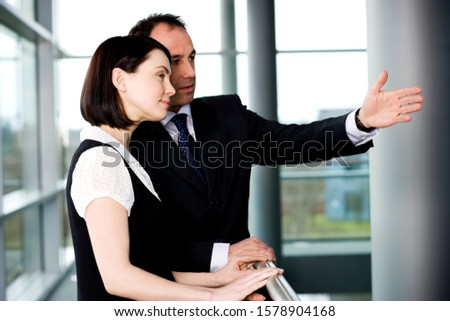 Businessman with female colleague or client in office #1578904168