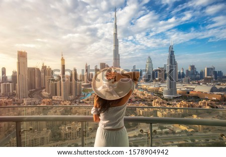 Woman with a white hat is standing on a balcony in front of the skyline from Dubai Downtown Royalty-Free Stock Photo #1578904942