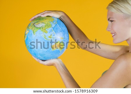 A Young Woman Holding A Globe #1578916309