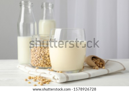 Glass of soy milk, soybeats seeds, bottle with milk on white background, space for text #1578926728