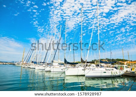 Row of docking yachts in calm port, holiday resort during summer with interesting sky #1578928987