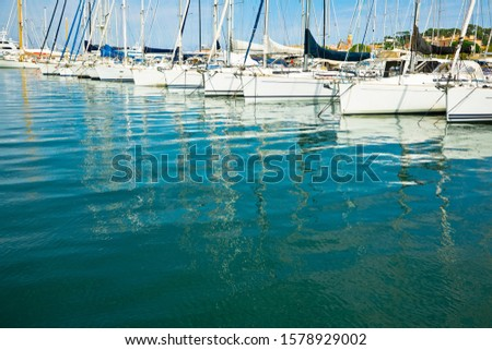 Reflection of docking yachts on the surface of calm water #1578929002