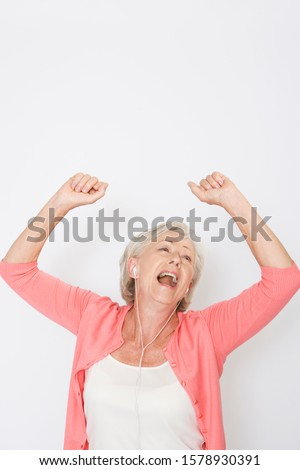A senior woman dancing to music on an mp3 player #1578930391