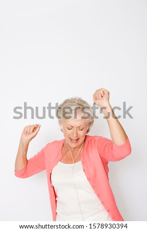 A senior woman dancing to music on an mp3 player #1578930394