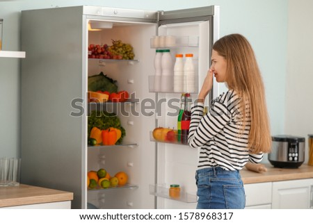 Woman feeling bad smell from fridge in kitchen #1578968317