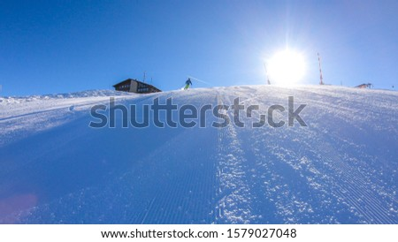 A skier going down the slope in Goldeck, Austria. Perfectly groomed slopes. The crispy snow is thrown up under the pressure of the ski. Man wears green trousers, blue jacket and helm for protection #1579027048