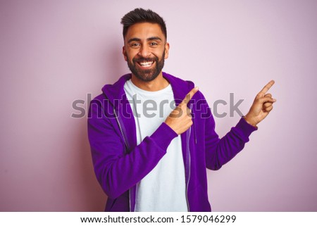 Young indian man wearing purple sweatshirt standing over isolated pink background smiling and looking at the camera pointing with two hands and fingers to the side. #1579046299