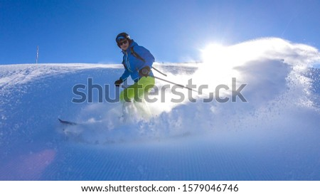 A skier going down the slope in Goldeck, Austria. Perfectly groomed slopes. The crispy snow is thrown up under the pressure of the ski. Man wears green trousers, blue jacket and helm for protection #1579046746