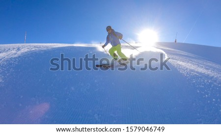 A skier going down the slope in Goldeck, Austria. Perfectly groomed slopes. The crispy snow is thrown up under the pressure of the ski. Man wears green trousers, blue jacket and helm for protection #1579046749