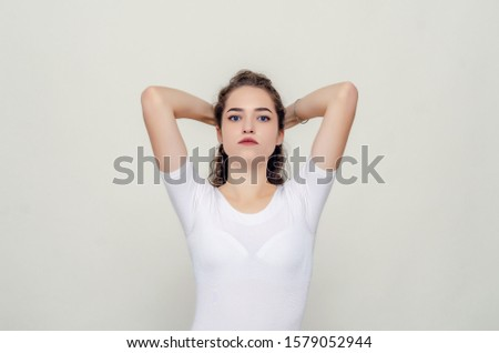 Young pretty girl gathered hair from behind, elbows forward, hands behind head. #1579052944