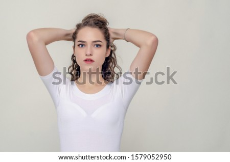 Young pretty girl gathered hair from behind, elbows forward, hands behind head. #1579052950