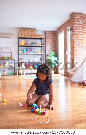 Beautiful toddler girl sitting on the floor playing with train at kindergarten #1579100158