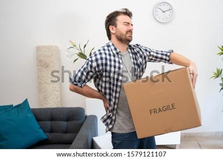 Man feeling back ache cramp lifting heavy boxes Royalty-Free Stock Photo #1579121107