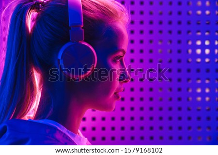 Image closeup of beautiful young caucasian woman listening to music with headphones over purple neon illumination indoors #1579168102