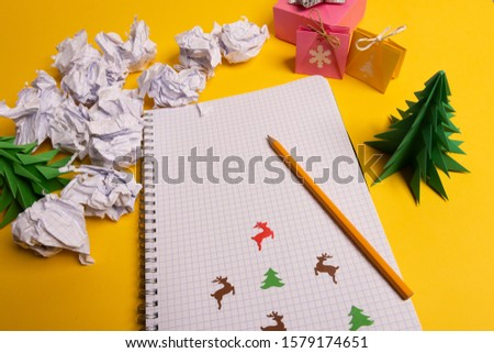 gift box and green paper origami trees with notepad on yellow desk, table. Christmas to do list text. #1579174651