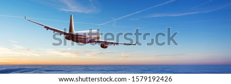Passengers commercial airplane flying above clouds in sunset light. Concept of fast travel, holidays and business. #1579192426