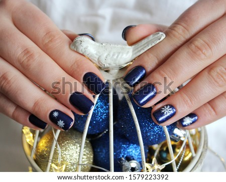 Stylish trendy female manicure. Neon blue nails on blue and white background. Nail polish. Art manicure. Modern style. Christmas manicure with snowflakes #1579223392