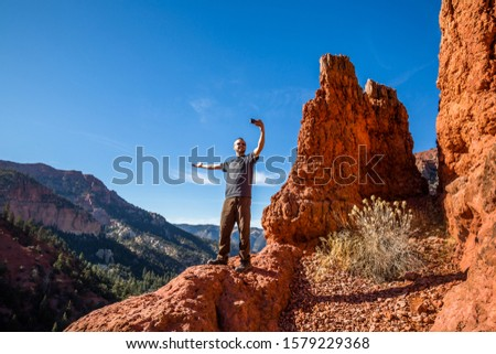 Excited hiker taking a selfie with an arm extended to show off the view behind him. Social media photos of active people. #1579229368
