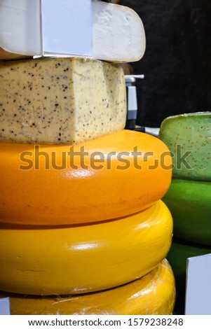 Multi colored cheese wheels on counter top for sale during Christmas fair festival. Various types of hard and soft cheese mix. Gouda, elemental, pesto, spices and nuts #1579238248
