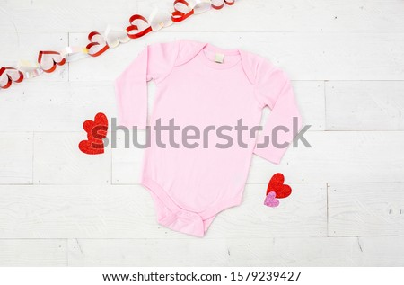Blank pink long sleeve baby girl bodysuit on white background with heart decor, baby apparel valentine's day mockup