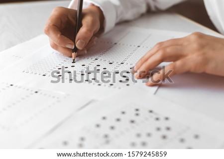 Student fills an exam test. #1579245859