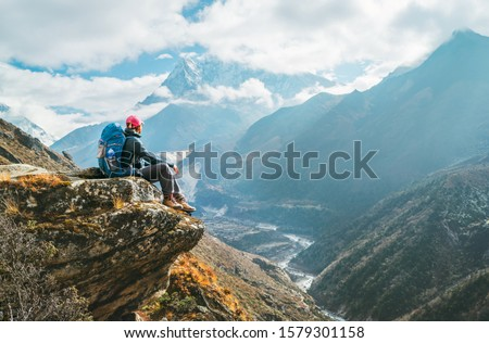 Young hiker backpacker female sitting on the cliff edge and enjoying Ama Dablam 6,812m peak view during Everest Base Camp (EBC) trekking route near Phortse, Nepal. Active vacations concept image #1579301158