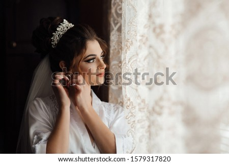 Bride with elegant hairstyle and makeup near the window. The bride corrects the earring. Beautiful earrings and hands of the bride. Happy woman bride in home prepared to wedding ceremony. #1579317820