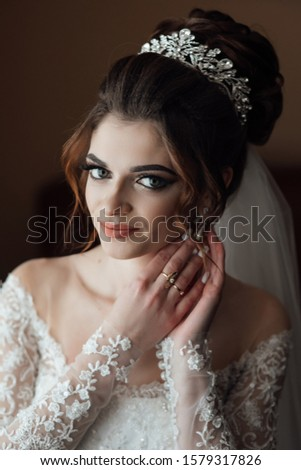 Cute bride with beautiful big green eyes. Beautiful bride with stylish make up and hair style with crown. Wedding photography. Morning of the bride. Bride hands near face. Bride's preparation at home #1579317826