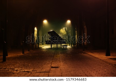 Piano music background.Grand Piano in the street of the city at night with street lamps and cobblestone floor