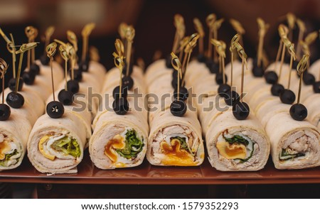Beautifully decorated catering banquet table with different food snacks and appetizers on corporate christmas birthday party event or wedding celebration, different vegan vegetarian snacks #1579352293