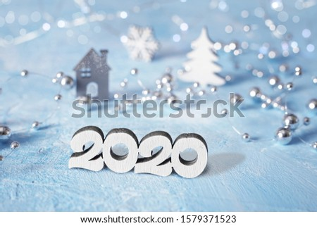 New Year figures 2020 on a blue snowy background with bright lights. Happy New Year card, template, blank for design. The symbol of the coming of next year.