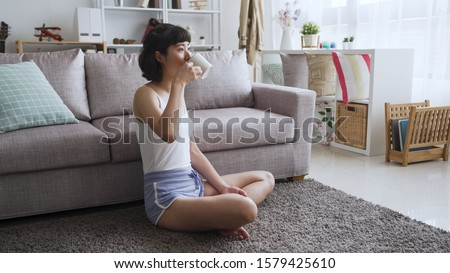 Attractive Asian japanese woman drinking coffee in mug leaning on sofa couch. cheerful young cute girl enjoy hot tea in morning. pretty lady sitting on carpet on floor in summer break at home #1579425610