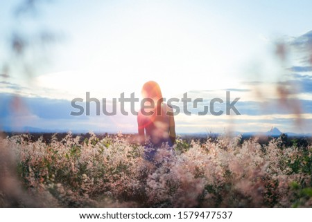 Trendy girl in stylish summer dress feeling free in the field with flowers in sunshine.