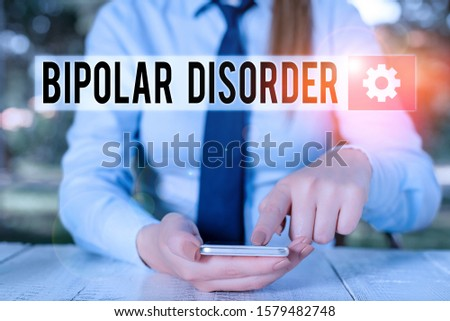 Conceptual hand writing showing Bipolar Disorder. Business photo showcasing mental illness that brings severe high and low moods Female business person sitting and holding mobile phone. #1579482748