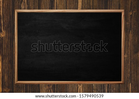 Abstract blackboard or chalkboard with frame on wooden background. empty space for add text. #1579490539