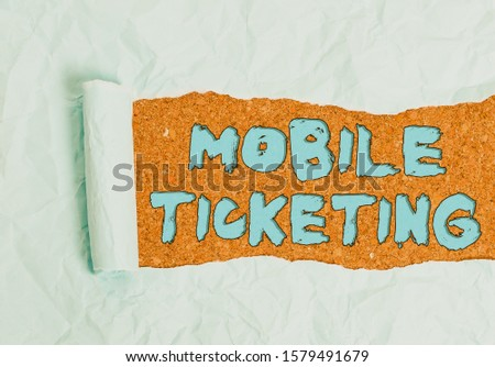 Word writing text Mobile Ticketing. Business concept for tickets arrive as a text message with a special barcode Cardboard which is torn in the middle placed above a wooden classic table. #1579491679