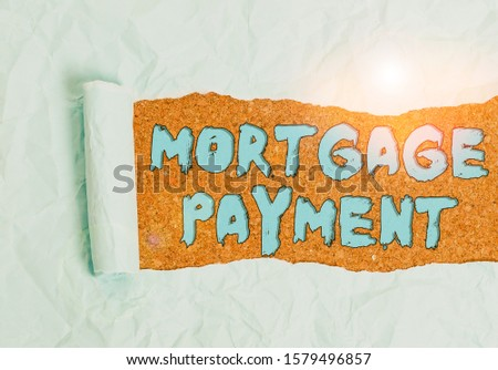 Word writing text Mortgage Payment. Business concept for periodic amount paid to a holder for repayment of a loan Cardboard which is torn in the middle placed above a wooden classic table. #1579496857
