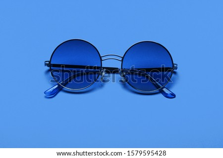 Beautiful trendly sunglasses on a Classic Blue Pantone color of the year background